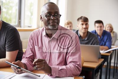 Naklejka Dojrzały uczeń za pomocą cyfrowego tabletu w klasie edukacji dorosłych