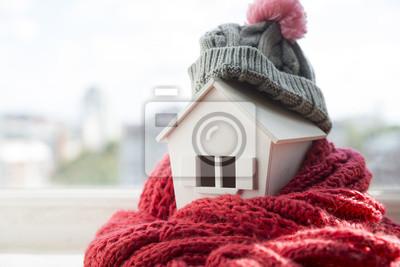 Naklejka dom w zimie - koncepcja systemu grzewczego i zimna śnieżna pogoda z modelem domu w czapce z dzianiny