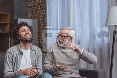 Naklejka dorosły syn i starszy ojciec rozmawiają i śmieją się w domu