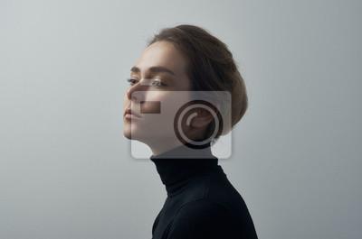 Naklejka Dramatyczny portret młodej pięknej dziewczyny z piegami w czarnym golfie na białym tle w studio