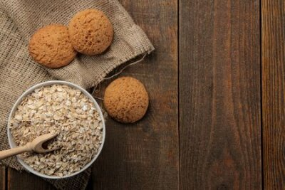 Naklejka Dry oatmeal and oatmeal cookies in a white bowl and a wooden spoon. food. healthy food. on a brown wooden table. top view with space for inscription