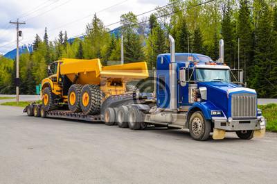 Naklejka Duża ciężarówka z naczepą niskopodwoziową przewożącą wywrotkę na publicznym parkingu postoju dla ciężarówek