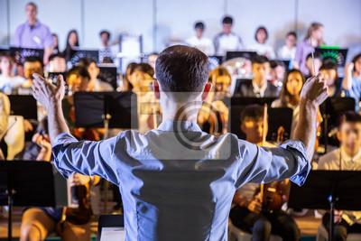 Naklejka Dyrygent męskiej szkoły dyrygował swoim zespołem studenckim do wykonywania muzyki na szkolnym koncercie