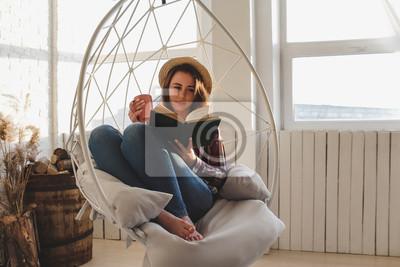 Naklejka Dziewczyna relaksuje czyta książkę i pije herbaty.
