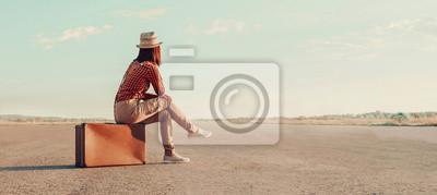 Naklejka Dziewczyna samotnie siedzi na walizka na drogach