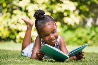 Naklejka Dziewczynka czyta książkę w parku