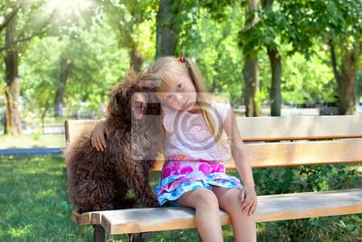 Dziewczynka przytulanie psa pudel w parku