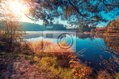 Early misty morning. Sunrise over the lake in autumn