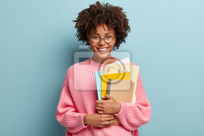 Naklejka Education and ethnicity concept. Optimistic glad dark skinned young woman with pleased expression, holds textbooks nad papers, rejoices learning new information, isolated over blue background