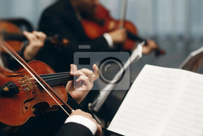 Naklejka Elegant string quartet performing at wedding reception in restaurant, handsome man in suits playing violin and cello at theatre play orchestra close-up, music concept