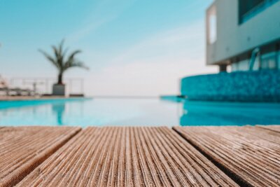 Naklejka Empty wooden deck with swimming pool , Beautiful minimalist pool side view with clear blue sky . Vintage filter color apply