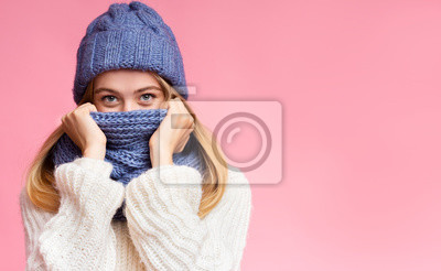 Naklejka Enigmatic winter girl hiding from cold over pink background