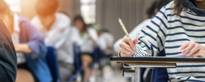 Naklejka Exam at school with student's taking educational admission test in class, thinking hard, writing answer in university classroom, education and world literacy day concept