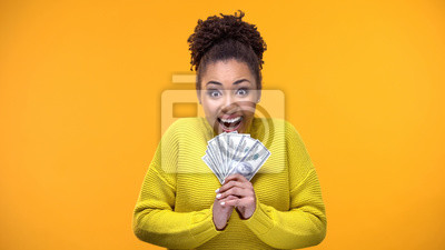 Naklejka Excited Afro-American woman holding bunch of dollars, lottery winner, fortune