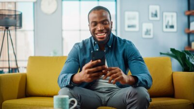 Naklejka Excited Black African American Man Using Smartphone while Resting on a Sofa in Living Room. Happy Man Smiling at Home and Chatting to Colleagues and Clients Over the Internet. Using Social Networks.