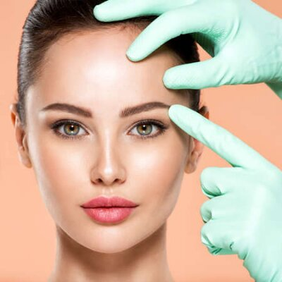 Naklejka Face skin check before plastic surgery. Beautician touching young woman face. Doctor in medicine gloves checks a skin before plastic surgery. Beauty treatments. Colorful image