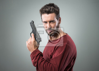 Fajny młody człowiek trzyma pistolet