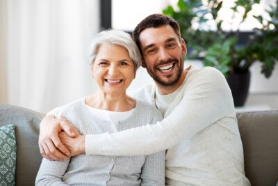 Naklejka family, generation and people concept - happy smiling senior mother with adult son hugging at home