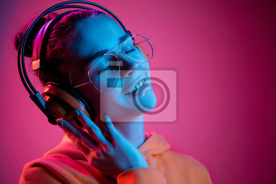 Naklejka Fashion pretty woman with headphones listening to music over red neon background at studio.