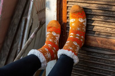 Naklejka Feet with orange socks supported by rustic wood texturizad