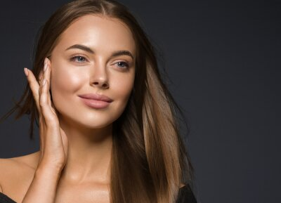 Naklejka Female face beauty woman long hair fly natural make up clean healthy skin hand touching face