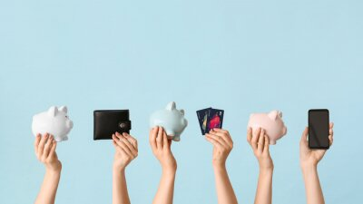 Naklejka Female hands with piggy banks, credit cards, wallet and mobile phone on color background. Concept of online banking