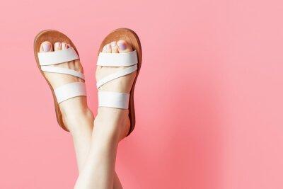 Naklejka Female legs in summer flip flops on pink background, copy space