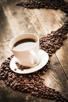 Naklejka Filiżanka kawy z ziaren kawy obok niej.