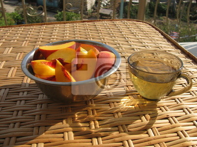 Filiżanka zielonej herbaty i talerz z plasterków brzoskwini