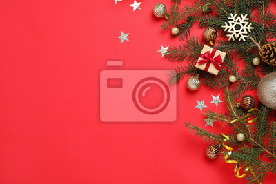 Naklejka Fir branches with Christmas decoration on red background, flat lay. Space for text