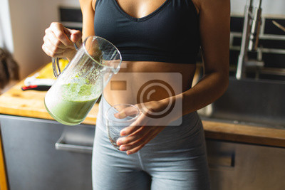Naklejka Fitness diet concept. Sporty woman drinking a green detox smoothie for breakfast in the kitchen.