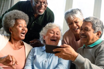 Naklejka Five happy diverse senior friends sitting on sofa and looking at smartphone