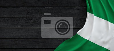 Naklejka Flag of the Nigeria, fabric on dark wood.