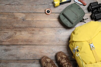 Naklejka Flat lay composition with tourist backpack and other camping equipment on wooden background, space for text