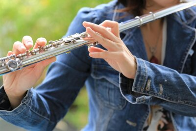 Naklejka Flute classical instrument player playing song. Instructor practicing bronze woodwind for orchestra as solo with green bokeh outside with nature.