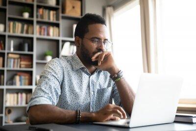 Naklejka Focused concentrated african businessman sit at desk look at laptop