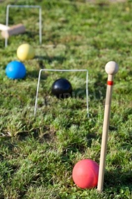 four balls in game of croquet on green lawn in summer day