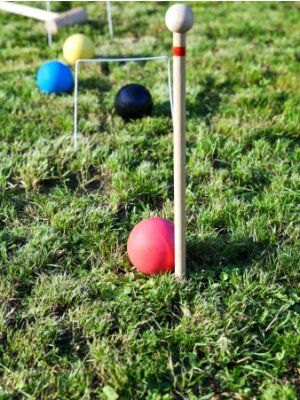 four balls on grass in game of croquet on green lawn in summer day