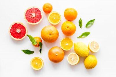 Naklejka Fresh citrus background. Oranges, grapefruits, leaves - whole fruits and halfs - on white background top-down