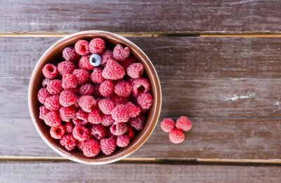 Naklejka Fresh raspberries in plate on a wooden table