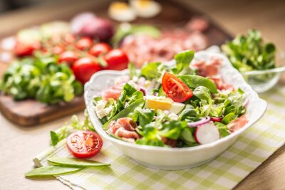 Naklejka Fresh spring salad with green leaves tomatoes egg radish red onion young peas prosciutto feta cheese and olive oil