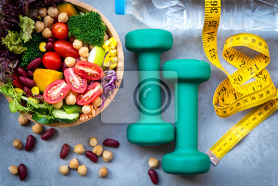 Naklejka Fresh vegetable salad and healthy food for sport equipment for women diet slimming with measure tap for weight loss on wood background. Healthy Sport Concept.