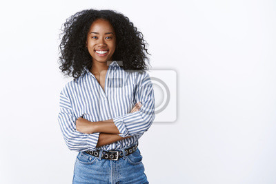 Naklejka Friendly cheerful attractive african american curly-haired young 25s woman consultant woking talking coworkers smiling pleasant having fun enjoying relaxing company mood, standing hands crossed chest