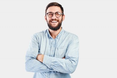 Naklejka Friendly face portrait of an authentic caucasian bearded man with glasses of toothy smiling dressed casual against a white wall isolated