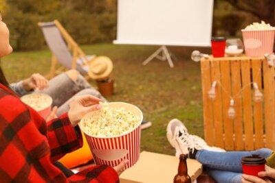 Naklejka Friends watching movie in outdoor cinema