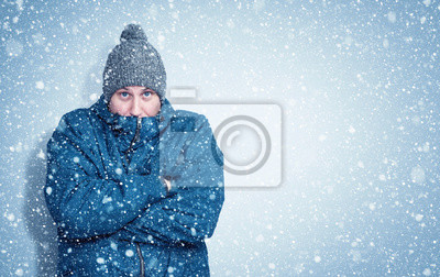 Naklejka Frozen man in a blue jacket and hat stands against the wall, snow is falling around