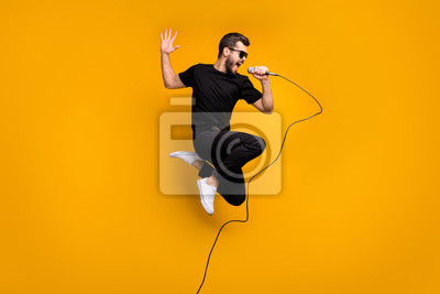 Naklejka Full body profile photo of crazy hipster guy jumping high holding microphone music lover singing favorite song wear sun specs black t-shirt pants isolated yellow color background