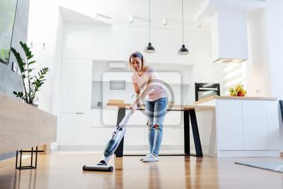 Naklejka Full length of worthy caucasian blonde housewife using steamer to clean floor in living room.