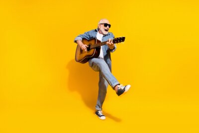 Naklejka Full length photo of cool happy positive old man dance hold guitar wear sunglass isolated on yellow color background