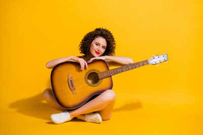 Naklejka Full size photo of pretty lovely young musician girl sit hold guitar crossed legs country music star wear red singlet uncovered shoulders isolated vibrant yellow color background